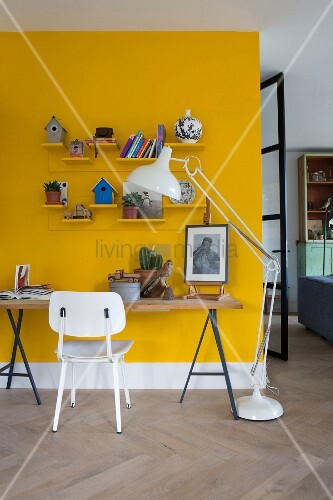 Tabletop on metal trestles against yellow wall, white-painted retro chair and modern standard lamp to one side