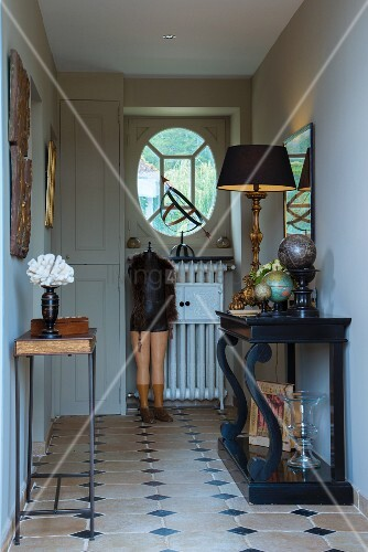 Table lamp on antique black console table and nostalgic tailors' dummy in traditional country-house hallway