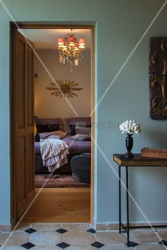 View from hallway through open bedroom door of chandelier with small lampshades above bed