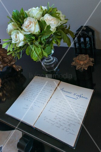 Open diary and glass vase of white roses on table