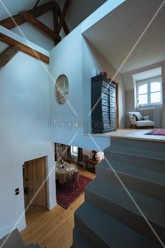 Concrete staircase without handrail leading to gallery in converted attic with view into lower storey