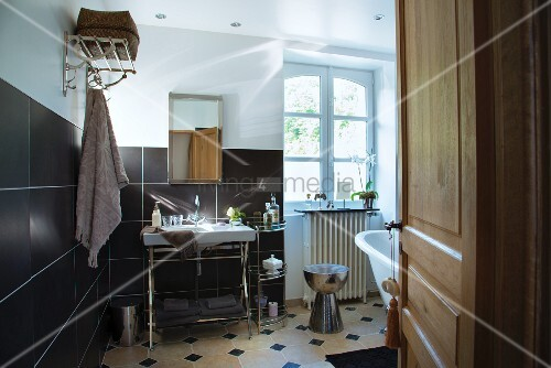 Washstand against wall with black-tiled dado and white lattice window in renovated country-house bathroom