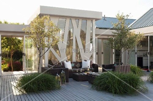 Trees in large planters and modern, dark wicker outdoor furniture on terrace in front of steel and glass façade