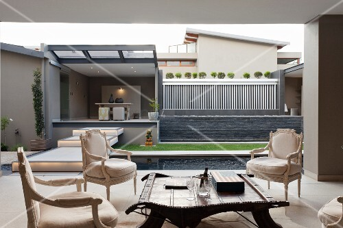 View from roofed lounge area to modern garden with pool