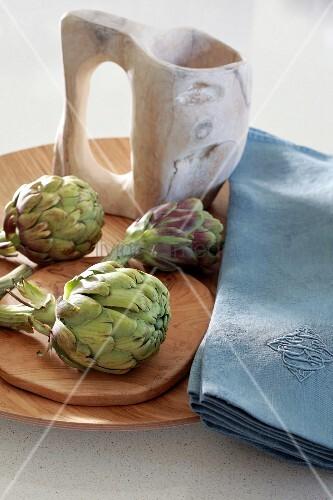 Artichokes, blue linen napkins and jug on wooden dish