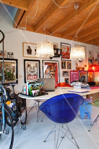 Blue, plastic retro shell chair at table, gallery of pictures on wall and bicycle to one side