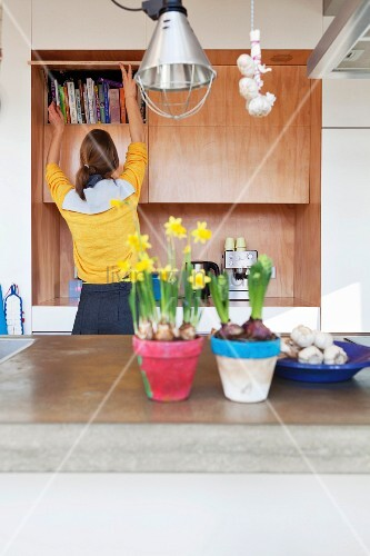 Blumentöpfe mit Narzissen und Hyazinthen auf Küchentheke, im Hintergrund Frau vor Bücherschrank aus Holz
