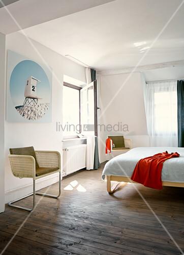 Freischwinger mit hellem Rattan Geflecht in schlichtem Schlafzimmer, rustikaler Dielenboden