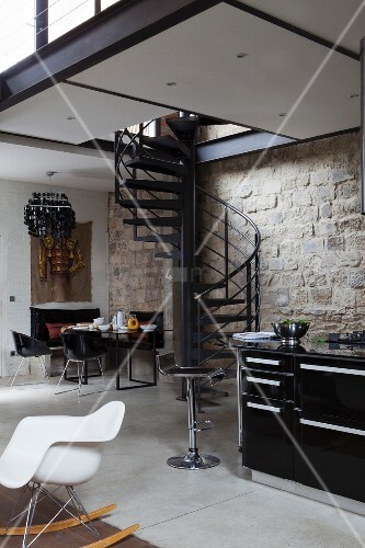 White classic rocking chair, kitchen counter, black metal spiral staircase and dining area below gallery against stone wall