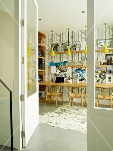 Arbeitszimmer mit langem Tisch und Klassiker Holzstühlen, an Wand Tapete mit Baummotiv