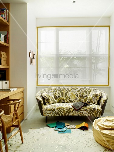 Geschwungenes Sofa mit Blumenmuster vor Fenster
