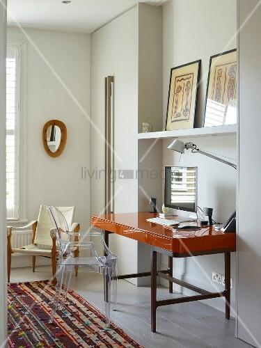 Schreibtisch mit hochglänzender Oberfläche auf Metallgestell in Wandnische, davor Ghost Stuhl