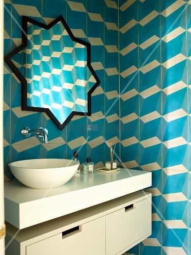 Moderner Waschtisch mit aufgesetzter Schüssel und sternenförmiger Spiegel, an gefliester Wand mit blau-weißem, dreidimensionalem Muster