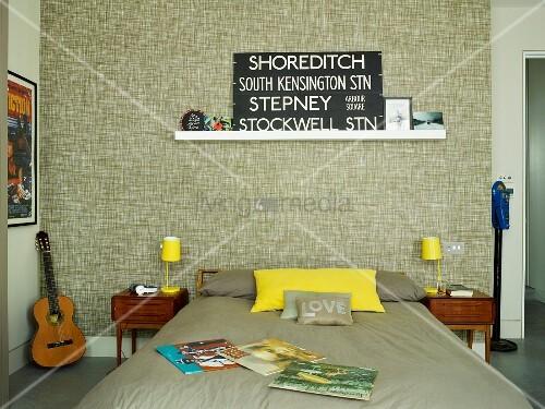 Dopppelbett mit Bettwäsche in Taupe, seitlich gelbe Tischleuchten auf filigranem Nachtkästchen, an tapezierter Wand