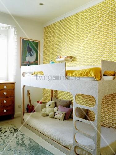 Etagenbett vor tapezierter Wand mit gelbem Retro Muster im Kinderzimmer