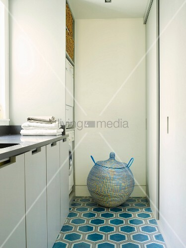 Kugelförmiger Korb mit Deckel auf gemustertem Fliesenboden im Waschraum