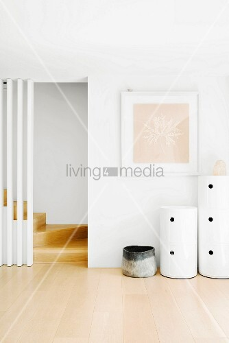 Bright, purist hallway with round containers next to foot of staircase