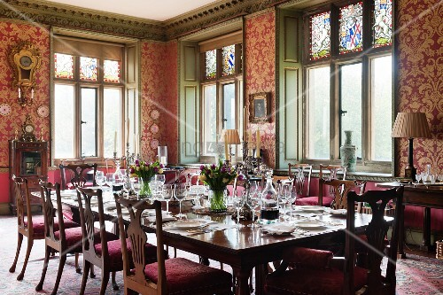 Festively Set Table In Grand Dining Room With Red And Gold Patterned  Wallpaper And Wood Panelled Window Reveals