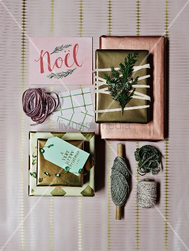 Christmas gifts wrapped in copper and gold-coloured paper with matching ribbons arranged on wrapping paper background