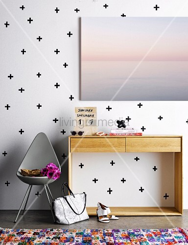 Hand-crafted plywood calendar on console table against white wall with pattern of black crosses