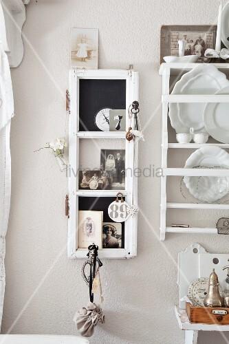 Schmaler Vitrinenschrank an pastellfarbener Wand aufgehängt, seitlich Wandregals mit weissen Dekotellern