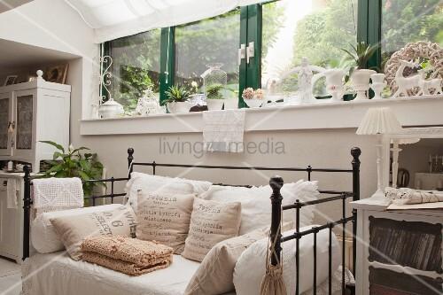Sitzbank mit schwarzem Vintage Metallgestell und Kissen unter Fensterband mit grün lackiertem Rahmen