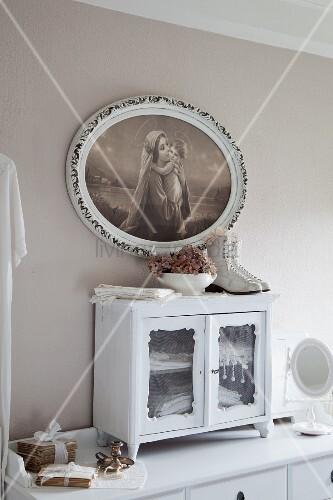 Kleines Vitrinenschränkchen auf Ablage, oberhalb Bild mit religiösem Motiv in ovalem Rahmen an pastellgrauer Wand