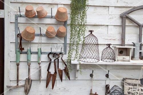 An weiss gestrichenem Holzpaneel aufgehängte Gartenwerkzeuge und Bluemntöpfe