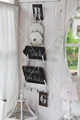 In Zimmerecke aufgehängter Topfdeckelhalter mit beschrifteten Tafeln, an weiss lasierter Holzwand