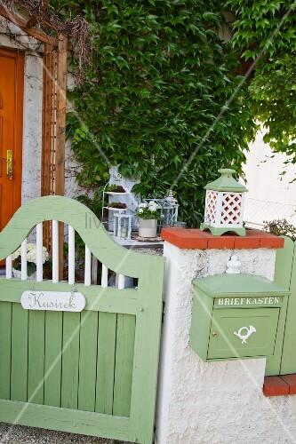 Grün lackiertes Holz Gartentürchen, neben Mauerstück mit aufgehängtem Briefkasten in gleicher Farbe