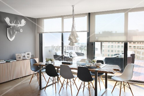 essplatz mit eames chairs vor fensterfront in penthouse wohnung deko geweih an der wand bild. Black Bedroom Furniture Sets. Home Design Ideas