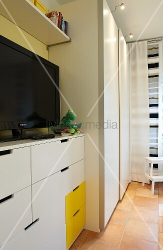 A white bedroom with yellow accents and a television on top of a chest of drawers next to a wardrobe