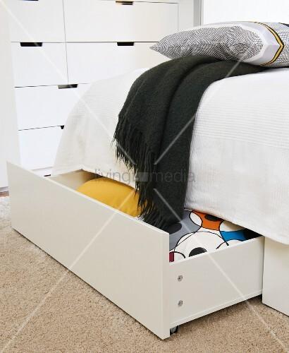 Stauraum für Decken und Kopfkissen in großen Auszügen unter dem Bett; Kommode im Hintergrund
