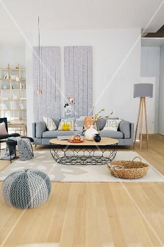 Sitzbereich durch Teppich und tapezierte Wandpaneele im Raum definiert; gestricktes Bodenkissen im Vordergrund