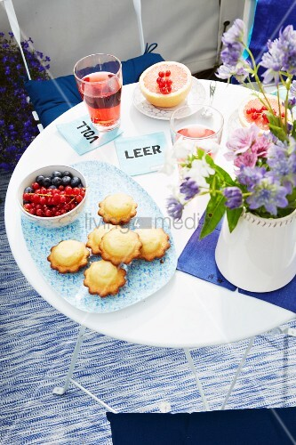 Cakes, fruit, drinks and a bunch of flowers on a folding table on a balcony