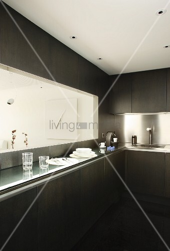 Designer kitchen with dark fronts, stainless steel splashback and hatch above narrow counter with view of modern artwork in dining area