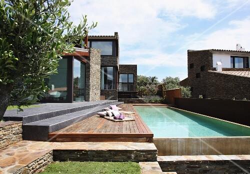 Steinstufen und Sonnendeck an langgestrecktem Pool zwischen modernen Ferienhäusern mit Natursteinfassade