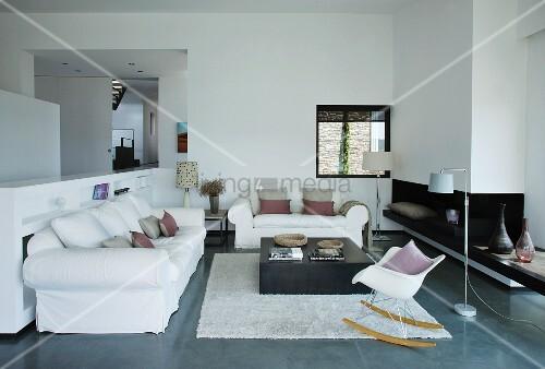 weiße Sitzgruppe vor Kamin in modernem Wohnraum; Klassiker Schaukelstuhl im Vordergrund