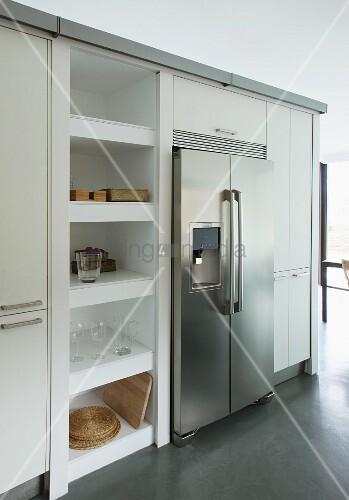 Doppeltüriger Kühlschrank aus Edelstahl, flankiert von Hochschränken und offenem Regal