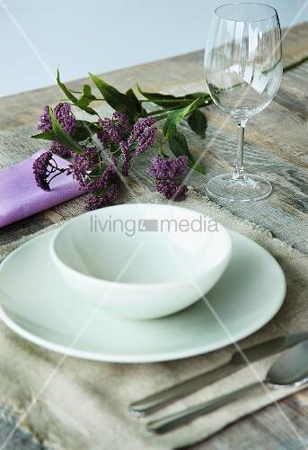 Weisses Gedeck auf Leinenset und Blumenzweig auf rustikalem Holztisch