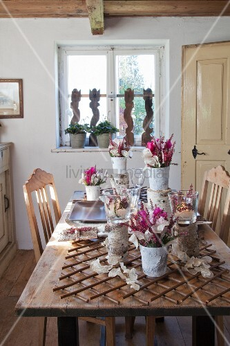 Vases and flowers arranged with natural materials on rustic table in simple dining room