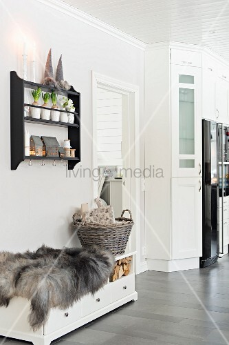 Animal-skin rug and basket on trunk with drawers and firewood compartment below hyacinths on narrow plate rack on wall
