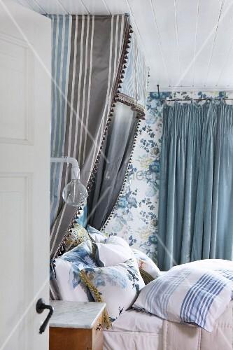 Romantisches Schlafzimmer In Blautönen, Bett Mit Vielen Kissen, Baldachin  Mit Graublau Gestreiftem Vorhang Und Blumentapete