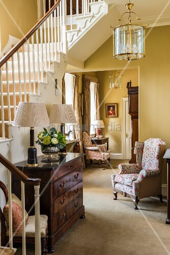 Antique chest of drawers at foot of staircase and floral armchair in classic foyer