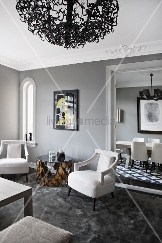 Elegant white armchairs and side table in corner of grey-painted lounge; open door with view of dining area in background