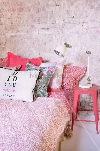 Bett mit rotweiß gemusterter Tagesdecke und Kissen, seitlich rosa lackierter Klassiker-Metallhocker im Retrostil mit Nachttischlampe vor Ziegelwand