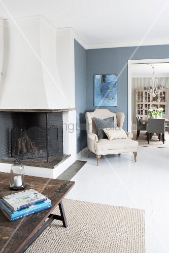 Open-plan living area with fireplace and elegant armchair in corner against slate grey walls