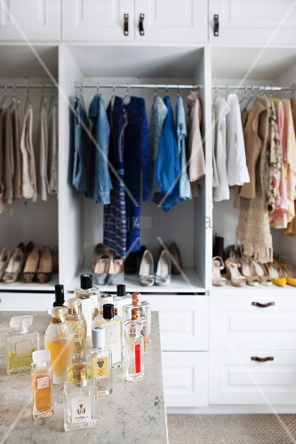 Various bottles of perfumes in front of ladies' shoes and clothes in open-fronted wardrobes