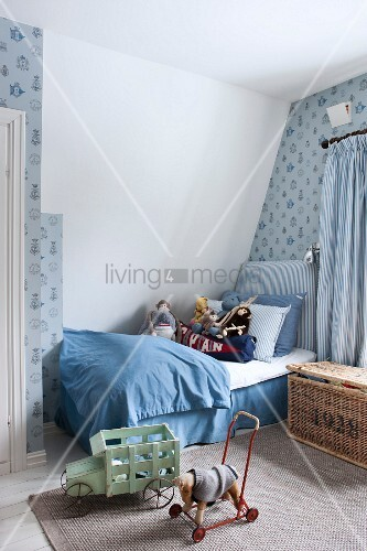 Boy's bedroom in shades of blue with soft toys, patterned wallpaper and vintage-style toys