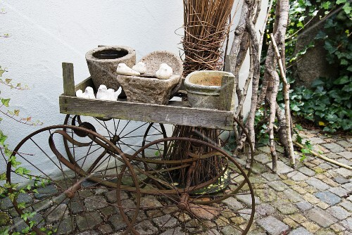 Various planters in wooden crate on antique pram frame